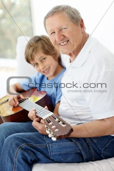 Little boy playing guitar with his grandfather