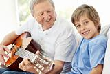 Mature man playing guitar with his grandson
