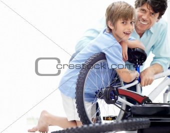 Little boy repairing his bicycle with his father
