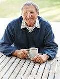 Old man sitting outdoors with a cup of coffee