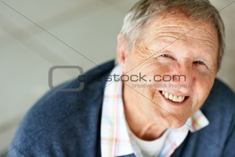 Portrait of smiling old man looking up at you