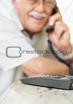 Portrait of old man using a telephone
