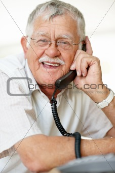 Smiling aged man making a phone call