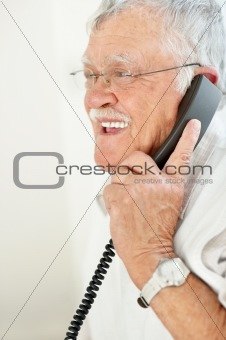 Relaxed aged man using  telephone