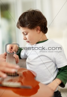 Little boy learning to play acoustic guitar at home