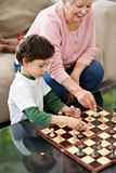 Portrait of adorable boy playing chess with his grandmother