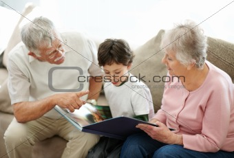 Boy and his grandparents reading a story together