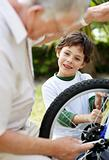 Cute boy watching his grandfather fixing a bicycle tyre