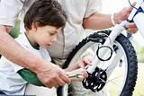 Portrait of cute little boy fixing his bicycle tyre