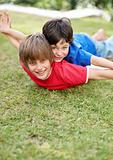 Sweet little kid lying on ground and his younger brother on back with hands outstretched