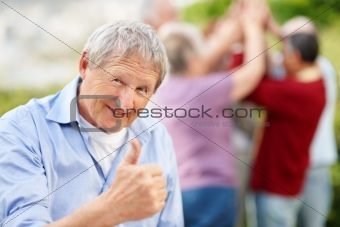 Happy old man showing thumbs up sign
