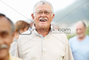 Old man enjoying outside with people in background