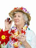Portrait of a happy old woman tourist wearing garland and blowing