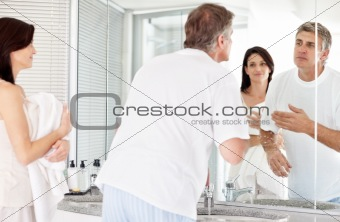 Man in washroom looking in mirror while his wife holding towel