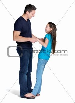 Portrait of a cute small girl standing on her father feet