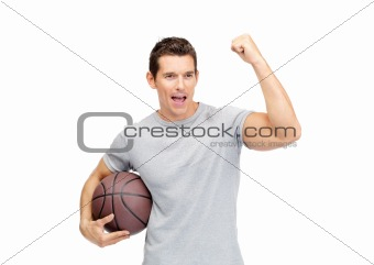 Portrait of an excited young man holding a basket ball and cheering