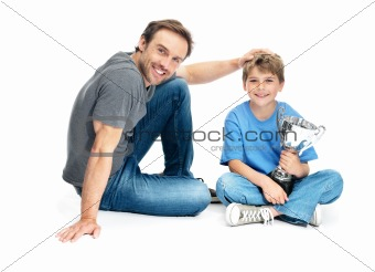 Portrait of a happy young father and his son with winning trophy