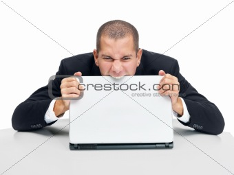 Frustrated young businessman biting the laptop