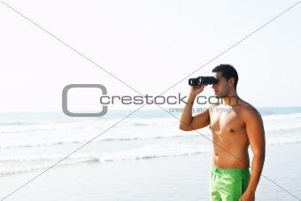 boy with binoculars  looking at the seashore