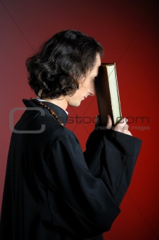 conceptual portrait of Praying priest with wooden cross reading