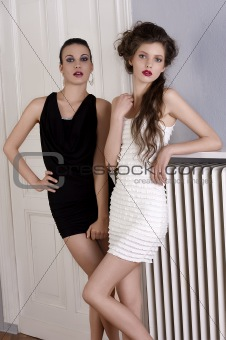 Beautiful girls in black and white dress posing towards the came