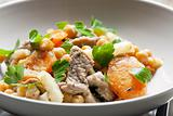 pork meat on celery with carrot and chick peas