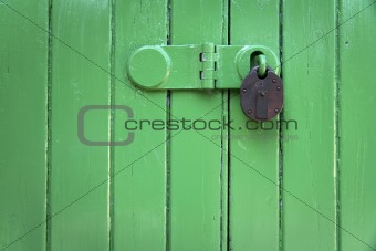 green wooden door rusty padlock