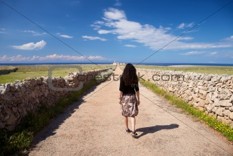 woman walking rural road to lighthouse