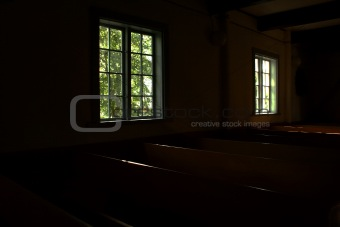 Dark rooms of church lighted by windows