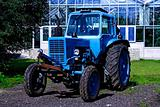 Painted in blue tractor standing before building