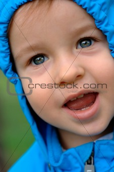 Smiling baby in a  raincoat