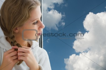beautiful  young girl braids her hair by the window