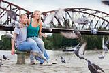 young happy couple sitting by the riverside, feeding birds