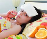 Sick young girl with a thermometer in bed