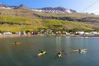 Tourist in Kayak. In background Seydisfjordur village - Iceland