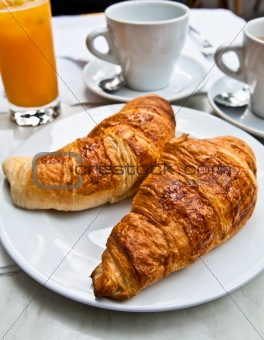 Breakfast with coffee and croissants on table