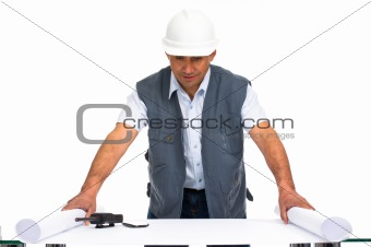 engineer with white helmet and blueprints