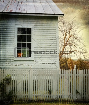 Old farm  house with pumpkin in the window