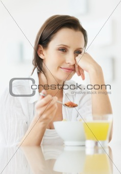 Woman sitting at the kitchen counter and eating a bowl of cut fruits