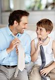 Young father and his son holding necktie and looking at each other