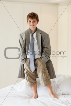 Portrait of a little boy wearing an oversized coat standing