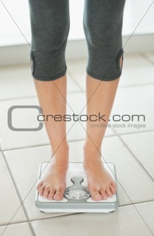 Low section of a young standing on a weighing scale