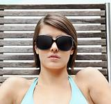 Young female wearing sunglasses while relaxing on a reclin