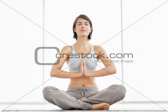Young fitness woman practicing yoga in the lotus pose