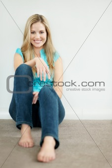 Happy relaxed young female sitting against wall with copy space