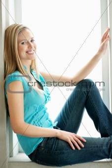 Side view of a casual young woman sitting and smiling