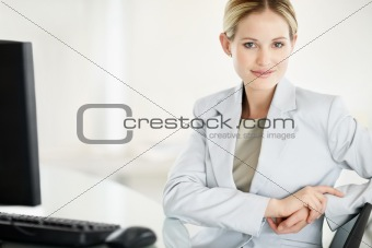 Confident young business woman with computer in office