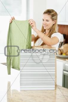 Woman with shopping bags at home , looking at new top