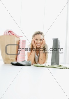 Smiling girl lying on floor with shopping bags - copyspace