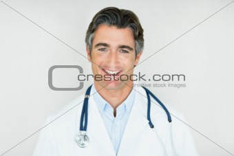 Smiling mature male doctor with stethoscope